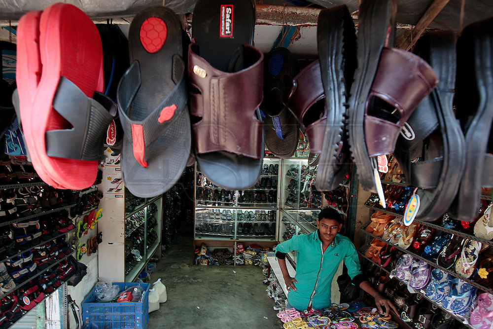 A shop keeper waits for some customers inside his show store.  The slum of Cheetah Camp on the outskirts of Mumbai, India is a predominantly muslim community on living on the fringe while the city continues to grow.
