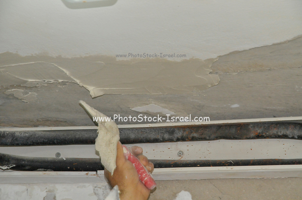 Home care. a room is being re plastered using a Putty knife. The plaster was redone due to dampness in the wall that allowed the growth of mould