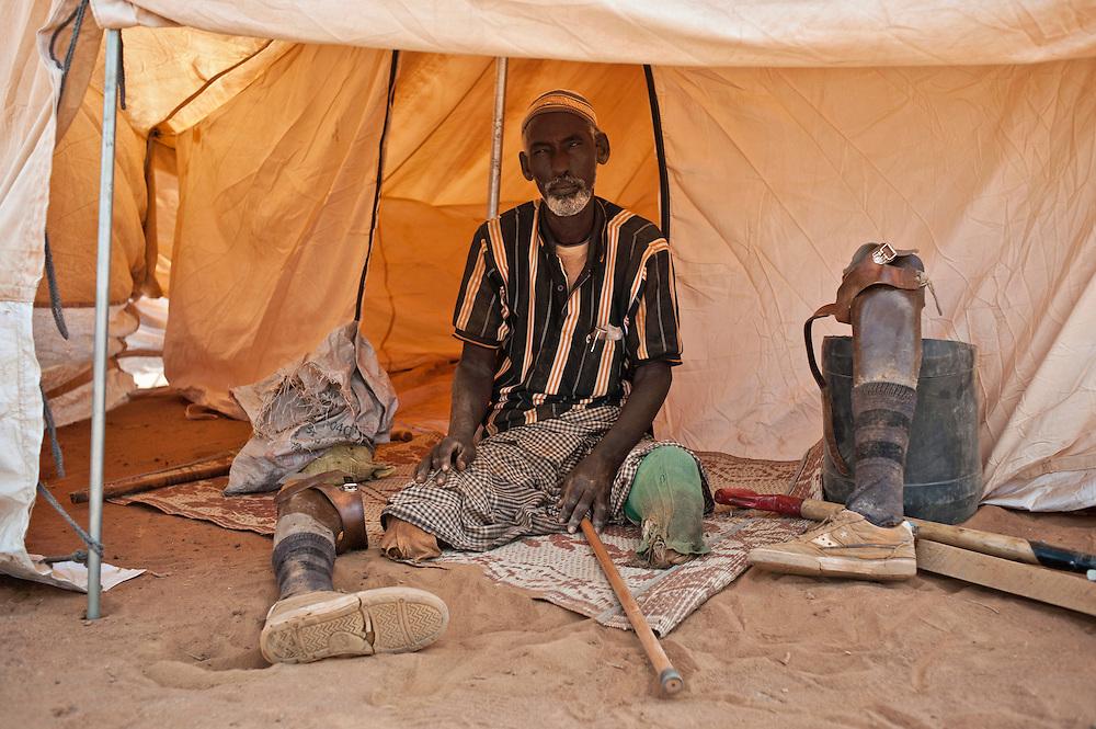 Camp de Ifo. Mahmoud Al Hussein, 50 ans, de Mogadiscio.  Mahmoud a échappé aux représailles des shebabs, actuels opposants au régime de transition. Ce soldat de l'ancien gouvernement était personellement visé. Les combattants ont tué sa femme. Il a dû fuir. Mohamed a perdu ses jambes sur une mine en 1992, en Somalie. Il porte désormais deux prothèses de bois. Désormais pour s'occuper la journée, il veille sur les toilettes. Il les répare si besoin, il a les outils pour. Il le fait gratuitement  parce qu'il sait à quel point les latrines sont un élément important d'hygiène dans le camp. Il a demandé à bénéficier d'une chaise roulante auprès de Handicap International, mais les procédures sont très longues. Il n'est pas sûr de vouloir retourner en Somalie, même si le pays retrouvait la paix.