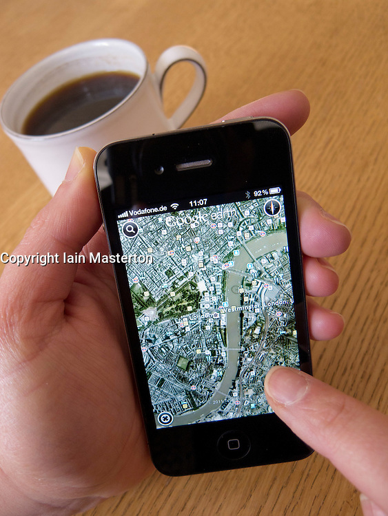 Woman looking at Google Earth map of London on an Apple iphone 4G smart phone