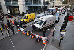 © Licensed to London News Pictures. 25/10/2021. London, UK. Insulate Britain activists block traffic on Bishopsgate in the City of London. The group have restarted their actions to block motorways and major roads causing disruption in the week before the COP26 climate meeting in Glasgow on 31/10/2021. Photo credit: Peter Macdiarmid/LNP