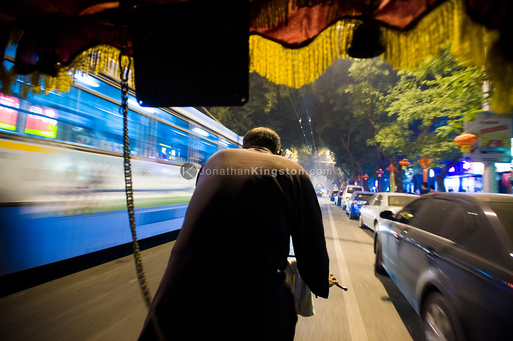 Night time point of view image from the seat of a bicycle rickshaw on the streets of Beijing, China.