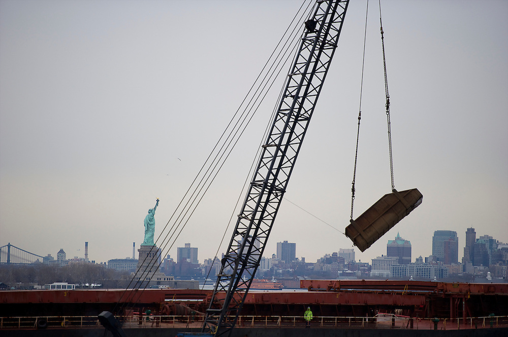 With the Statue of Liberty in the background, cranes and heavy machinery load piles of shredded metal material onto a tanker for overseas sale, at Sims Metals Management, the busiest metal recycling facility in the world, in Jersey City, NJ on March 21, 2013,