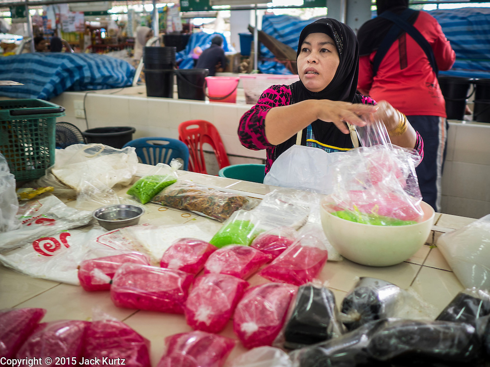 18 JUNE 2015 - PATTANI, PATTANI, THAILAND: A Thai Muslim woman sells traditional desserts and sweets in the market in Pattani. Many Thai Muslims go shopping early in the day to buy food for Iftar, the meal that breaks the day long Ramadan fast.    PHOTO BY JACK KURTZ