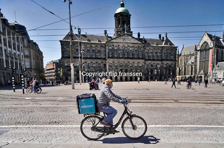 Nederland, Amsterdam, 6-5-2020  Een werknemer, medewerker van maaltijdbezorgdienst deliveroo fietst met zijn mandje achterop over de Dam om een bestelling af te leveren . Hij heeft een mondkapje op om zichzelf en anderen te beschermen tegen het virus . .,fiets,fietsen,dam,deliveroo,bestelling,afleveren,koerier,fietskoerier,maaltijd,eten,maaltijdbezorging,versoepelen,versoepeling,  Foto: Flip Franssen