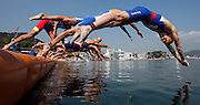 In this photo released by the International Triathlon Union, Russia's Dmitry Polyansky  (r ) leaps into the water to start the 2011 Tongyeong ITU Triathlon World Cup, on Saturday, October 15th. (AP Photo/ITU, Arnold Lim)