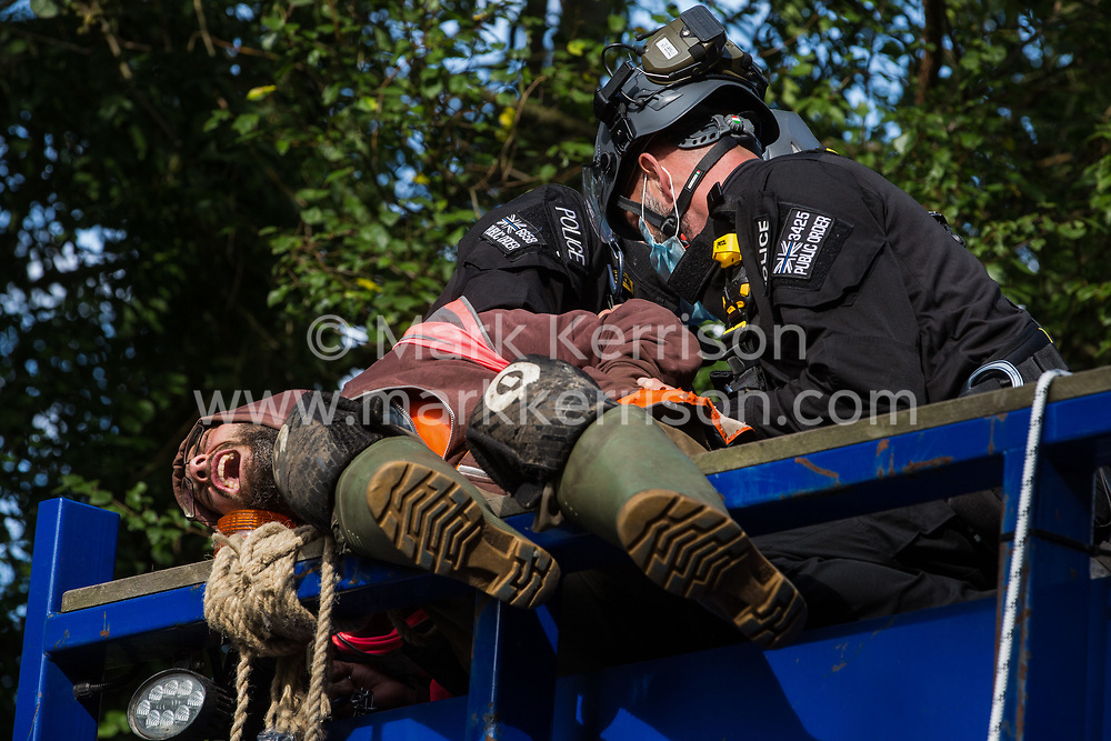 Denham, UK. 28th September, 2020. Thames Valley Police officers arrest an anti-HS2 activist who had glued himself to a HGV with a rope around his neck in order to block its passage to works for the HS2 high-speed rail link. Environmental activists continue to try to prevent or delay works on the controversial £106bn project for which the construction phase was announced on 4th September from a series of protection camps based along the route of the line between London and Birmingham.