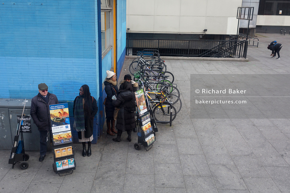 A group of Jehovah's Witnesses with Spanish language pamphlets and a person stopping to tie a shoelace at Elephant & Castle, Southwark, on 26th March 2019, in London, England