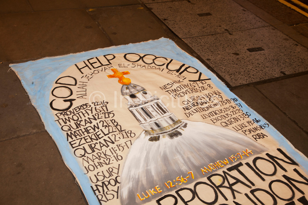 God Help Occupy banner. Police and protesters as eviction of the Occupy London OLSX camp takes place. The anti-capitalist demonstration that saw protesters camp outside St Paul's Cathedral in London was brought to an end by bailiffs and police. Protesters staging Occupy London were refused permission by the Court of Appeal last week to challenge orders evicting them from the cathedral steps, where they had been living in tents since October 15 last year. The City of London Corporation called on protesters to remove their tents voluntarily, but around 50 or 60 refused to budge. Some protesters created makeshift barriers out of wooden shelving units as police moved in to help bailiffs clear the camp. Police said 20 people had been arrested but the operation was largely peaceful.