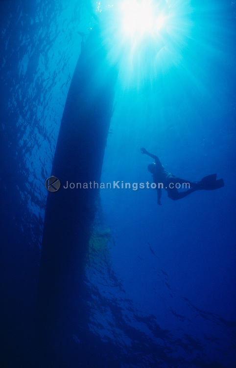 A lone SCUBA diver surfaces near his boat in the waters of the Andaman Sea.  Diving is one of the attractions bringing tourist dollars to these remote islands.