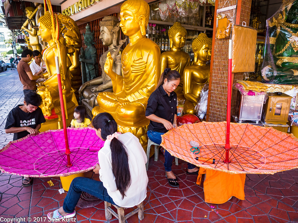01 FEBRUARY 2017 - BANGKOK, THAILAND: Women make large traditional parasols at a shop that makes and sells Buddhist paraphernalia in Bangkok. The umbrellas are used as parasols to keep the sun off important Buddha statues and at formal events. In Thai culture, the parasols were used to provide shade for members of the royal family or representatives of the royal family.     PHOTO BY JACK KURTZ