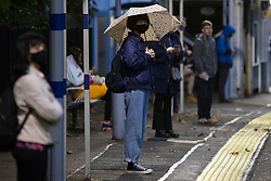 © Licensed to London News Pictures. 27/09/2021. London, UK. A commuter shelters under an umbrella during a rain shower at Maze Hill Station in Greenwich South East London. Rain showers are forecasted to continue in parts of London and South East England for the rest of the week.  Photo credit: George Cracknell Wright/LNP