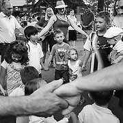"""Campers and visitors dance in a circle while holding hands during""""Collage"""" outside of Kresge Auditorium at Interlochen Center for the Arts in Interlochen, Michigan. """"Collage,"""" is one of Interlochen's most popular annual Camp events, showcasing a sample of student performances encompassing music, dance, theatre, creative writing, motion picture arts, and visual arts."""
