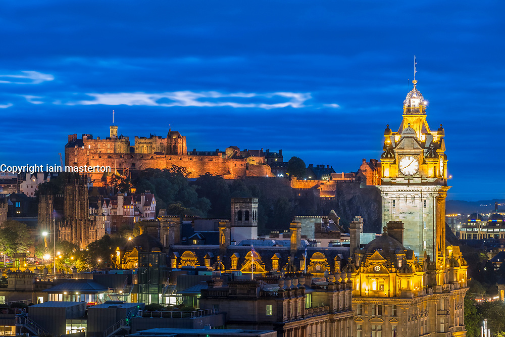 View of famous Edinburgh skyline with the castle to rear and Balmoral Hotel on right at dusk in Edinburgh, Scotland, United Kingdom.