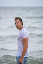 good looking man in a wet tee shirt and jeans standing in the ocean