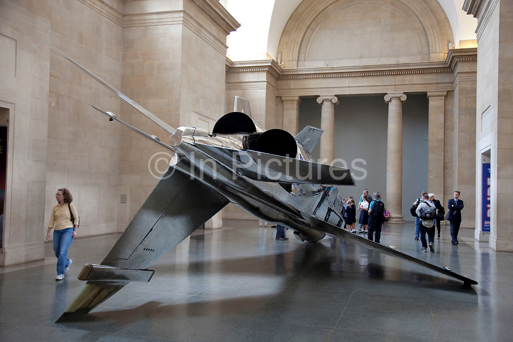 """Harrier and Jaguar, a grand scale art installation by artist Fiona Banner in the main space Duveen Galleries in Tate Britain gallery. The two stripped down decommissioned fighter jets dominate these great spaces. A Harrier Jump Jet, suspended from the ceiling painted with feint feathers, and the Jaguar, stripped of all ot's paint and polished to a gleaming high silver. Says the artist: """"I remember long sublime walks in the Welsh mountains with my father, when suddenly a fighter plane would rip through the sky , and shatter everything. It was so exciting, loud and overwhelming. It would really take our breath away. The sound would arrive from nowhere, all you would see was a shadow and then the plane was gone. At the time the Jump Jets were at the cutting edge of technology but to me they were like dinosaurs, prehistoric, from a time before words."""""""