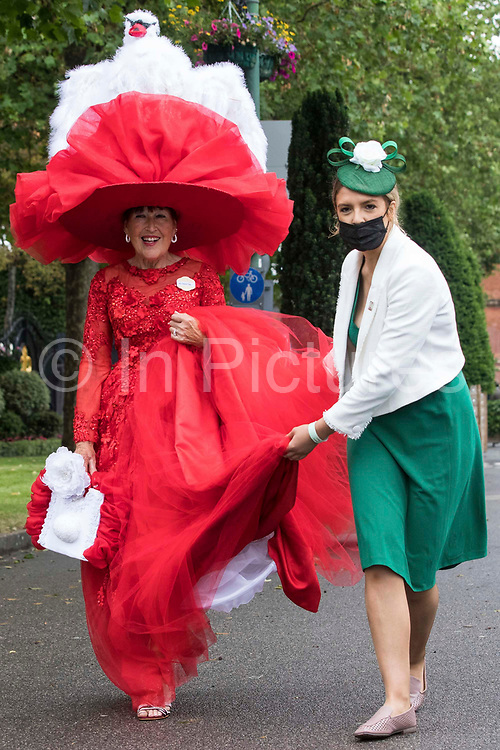 A stewardess assists racegoer Debra Day as she arrives wearing a red dress and a large red hat featuring a white swan on Ladies Day at Royal Ascot on 17th June 2021 in Ascot, United Kingdom. Despite Covid restrictions and changeable weather including some rain, many racegoers displayed the elaborate hats and fascinators for which Gold Cup Day has become well known.