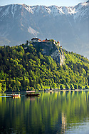 Pictures images photos of the  Medieval Bled Castle which stands above the lake on the north shore and has a museum with the alps behind. Lake Bled Slovania.<br /> <br /> Visit our PHOTO COLLECTIONS OF SLOVANIAN  HISTOIC PLACES for more photos to download or buy as wall art prints https://funkystock.photoshelter.com/gallery-collection/Pictures-Images-of-Slovenia-Photos-of-Slovenian-Historic-Landmark-Sites/C0000_BlKhcYWnT4Sites/C0000qxA2zGFjd_k