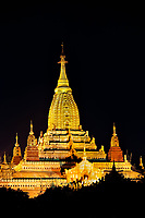 Ananda Gold: With the surrounding forest  as a silhouette, the Buddhist Ananda Temple shines as a golden jewel, set against the black night, Bagan Myanmar.