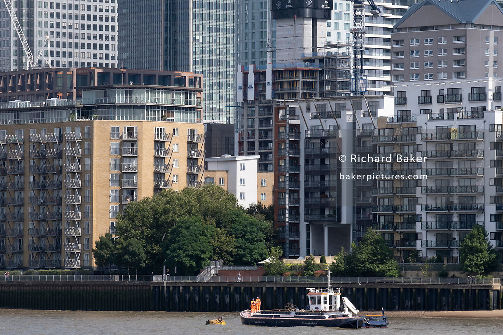 Two river workmen wearing high-vis clothing stand at the stern of their 'Port Of London Authority' boat beneath Thames riverside residential and office properties at Canary Wharf in London Docklands, on 16th September 2021, in London, England. Canary Wharf was once a thriving Victorian cargo dock but after Thames shipping declined from the 1960s, its derelict areas were redeveloped in the 19080 by Margaret Thatcher's Docklands Development Corporation created one of the UK's main financial centres, now home to the European Headquarters of numerous major banks including Barclays, Credit Suisse and HSBC.