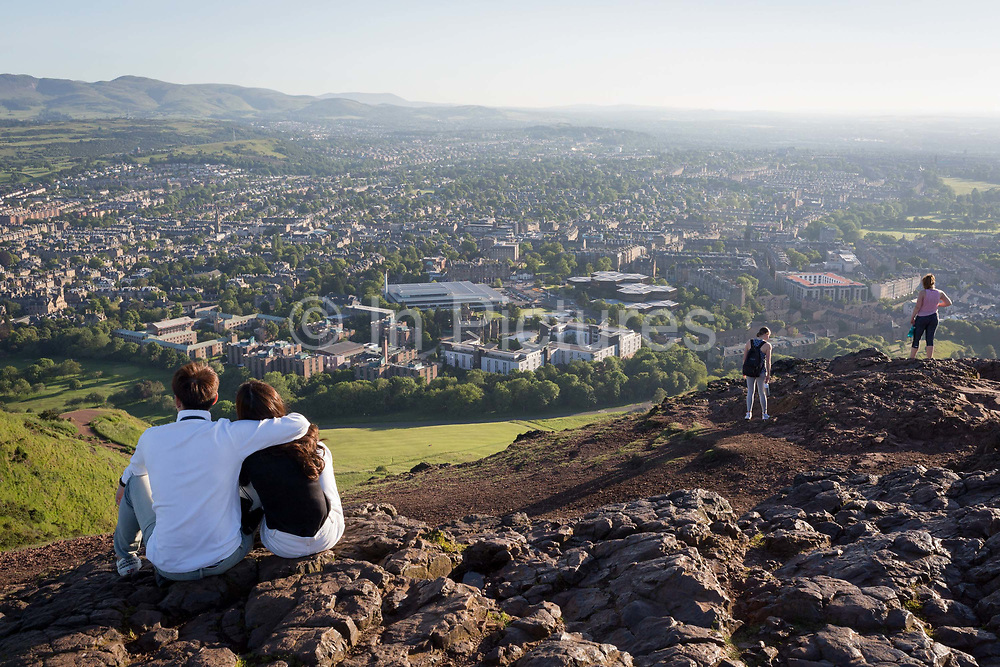 A young couple gaze out towards the city of Edinburgh from the summit of Arthurs Seat in Holyrood Park, on 26th June 2019, in Edinburgh, Scotland. Arthurs Seat is an extinct volcano which is considered the main peak of the group of hills in Edinburgh, Scotland, which form most of Holyrood Park, described by Robert Louis Stevenson as a hill for magnitude, a mountain in virtue of its bold design. The hill rises above the city to a height of 250.5 m 822 ft, providing excellent panoramic views of the city and beyond.