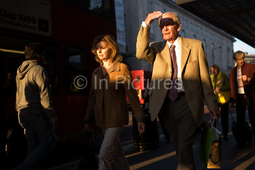 An elderly man shields his eyes from bright light while walking along Piccadilly in late afternoon sunshine. Holding his hand across his eyes, the man walks westwards along this fashionable shopping street from Piccadilly Circus in the direction of Hyde Park Corner. He seemingly walks alongside a younger woman and many other commuters are heading the same way, all walking or about to pause at the bus stops along this street that will take them home or in the direction of Victoria Station. The picture is shot from a low angle and the subjects are unaware of all but their direction, pace and eagerness to reach home.