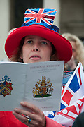 April 29th 2011 Royal Wedding. Trafalgar Square. Woman singing along holding official programme.