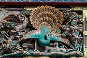 "Ornate peacock carved in wood. Toshogu Shrine is the final resting place of Tokugawa Ieyasu, the founder of the Tokugawa Shogunate that ruled Japan for over 250 years until 1868. Ieyasu is enshrined at Toshogu as the deity Tosho Daigongen, ""Great Deity of the East Shining Light"". Initially a relatively simple mausoleum, Toshogu was enlarged into the spectacular complex seen today by Ieyasu's grandson Iemitsu during the first half of the 1600s. The lavishly decorated shrine complex consists of more than a dozen buildings set in a beautiful forest. Countless wood carvings and large amounts of gold leaf were used to decorate the buildings in a way not seen elsewhere in Japan. Toshogu contains both Shinto and Buddhist elements, as was common until the Meiji Period when Shinto was deliberately separated from Buddhism. Toshogu is part of Shrines and Temples of Nikko UNESCO World Heritage site."
