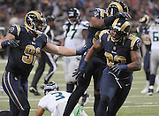 Football - NFL- Seattle Seahawks at St. Louis Rams.St. Louis Rams defensive end Eugene Sims (92, right) is congratulated by St. Louis Rams defensive end Chris Long (91, left) and St. Louis Rams defensive end Robert Quinn (94, behind Sims) after he sacked Seattle Seahawks quarterback Russell Wilson (3, on turf behind the trio) in the second quarter at the Edward Jones Dome in St. Louis.  The Rams defeated the Seahawks, 19-13.
