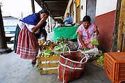31 MAY 2001 - ERONGARICUARO, MICHOACAN, MEXICO: A fruit vendor sells magoes to an Indian women in Erongaricuaro, on the shore of Lake Patzcauro, Michoacan, Mexico, May 31, 2001. Michoacan, one of Mexico's poorest states, has one of the highest rates of emigration to the US of any state in Mexico. Most of those who go north send money back to relatives in Mexico.    .PHOTO BY JACK KURTZ