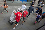 Two Evening Standard news distributors push a laden trolley with the first editions of the free London newspaper at Oxford Circus, on 17th July 2019, in London England.