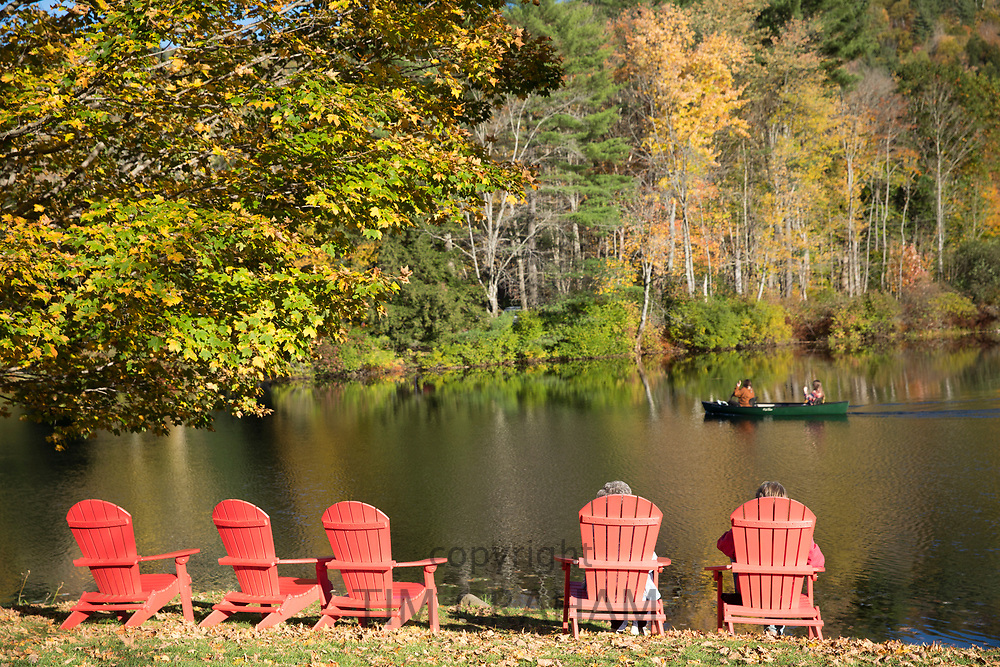 Tourists in Muskoka chairs, also knowns as Adirondack chairs and canoe on Lake Rescue near Ludlow in Vermont, New England, USA