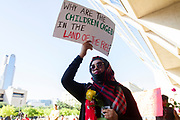 Ranya Ramim of Dallas, holds a protest sign during the Families Belong Together protest in front of Dallas City Hall in downtown Dallas. The protest was part of a national campaign  against the Trump administration's policy of separating the children of immigrants stopped at the border and housing them in tents in Tornillo Tx, a town near El Paso.