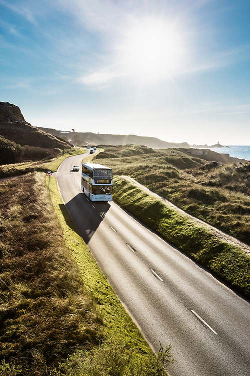 Double decker bus driving along the Five Mile Road through the sand dunes, which stretch along St Ouen's Bay in Jersey, CI