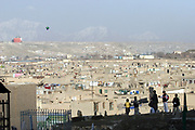 Noor Agha's children and students fly the kites next to their house inside the cemetery, Kabul, Afghanistan, Tuesday, March, 6, 2007. Noor Agha is a renowned kite maker who made kites for the movie makers of the best-selling novel, The Kite Runner, which will be distributed by Dreamworks and Paramount Vantage in Nov. this year. Noor Agha's wives, using their special glue, help him produce enough kites to please the clients' needs. Some of his children can also make their own kites with plastic bags and bamboo sticks. As the Afghan New Year's Day (Nawruz) approaching on March 21, the finger tips of Noor Agha's family got busier for mass production.