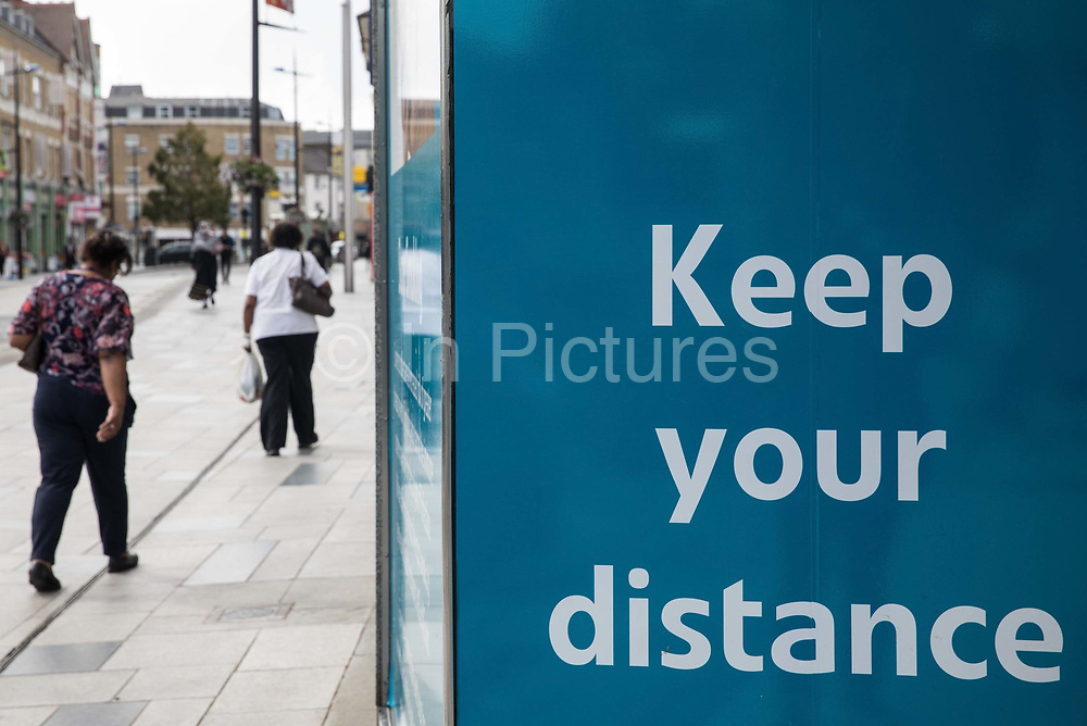 Members of the public walk past a COVID-19 social distancing display on 21st August 2020 in Slough, United Kingdom. Slough has been listed by Public Health England PHE and the Department for Health and Social Care DHSC as an 'area of concern' for COVID-19 following a rise in positive coronavirus cases over the last two weeks.