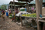 Wali-gara, women sellers, await customers with stacks of maniocs and other vegetables to sell on an elevated stall in a busy market area in a suburb of Bangui. Locals say these street markets have their own co-op, and the sellers pay dues to maintain their spot.