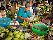 02 SEPTEMBER 2015 - BANGKOK, THAILAND: People shop for vegetables in the Bang Chak Market. The Bang Chak Market serves the community around Sois 91-97 on Sukhumvit Road in the Bangkok suburbs. About half of the market has been torn down, vendors in the remaining part of the market said they expect to be evicted by the end of the year. The old market, and many of the small working class shophouses and apartments near the market are being being torn down. People who live in the area said condominiums are being built on the land.         PHOTO BY JACK KURTZ