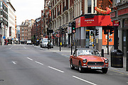 Vintage MG Midget drives along Shaftesbury Avenue on empty streets as lockdown continues and people observe the stay at home message in the capital on 12th May 2020 in London, England, United Kingdom. Coronavirus or Covid-19 is a new respiratory illness that has not previously been seen in humans. While much or Europe has been placed into lockdown, the UK government has now announced a slight relaxation of the stringent rules as part of their long term strategy, and in particular social distancing.