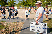 """08 AUGUST 2020 - WEST DES MOINES, IOWA: TOM WICKERSHAM leads a prayer for police officers and law enforcement in the parking lot of the West Des Moines Law Enforcement Center. About 100 people gathered at the West Des Moines Law Enforcement Center to rally in support of law enforcement. The rally was organized by """"Uplifting Our Police,"""" a local organization that supports law enforcement. They rallied at Des Moines Police headquarters in July. They are planning similar rallies at police stations in the Des Moines metropolitan area.       PHOTO BY JACK KURTZ"""