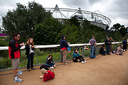 London 2012 Olympic Park in Stratford, East London. People sit and stand around eating their lunch with the Olympic stadium as a backdrop.