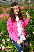 Young preteen girl of 12 in a hothouse of pink flowers