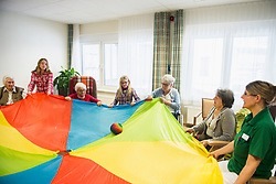 Nursing staff with girls and senior women doing sports exercise using parachute and ball in rest home
