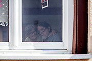 """An elderly pensioner couple is practising """"Social distance"""" behind a window during times of the corona virus."""