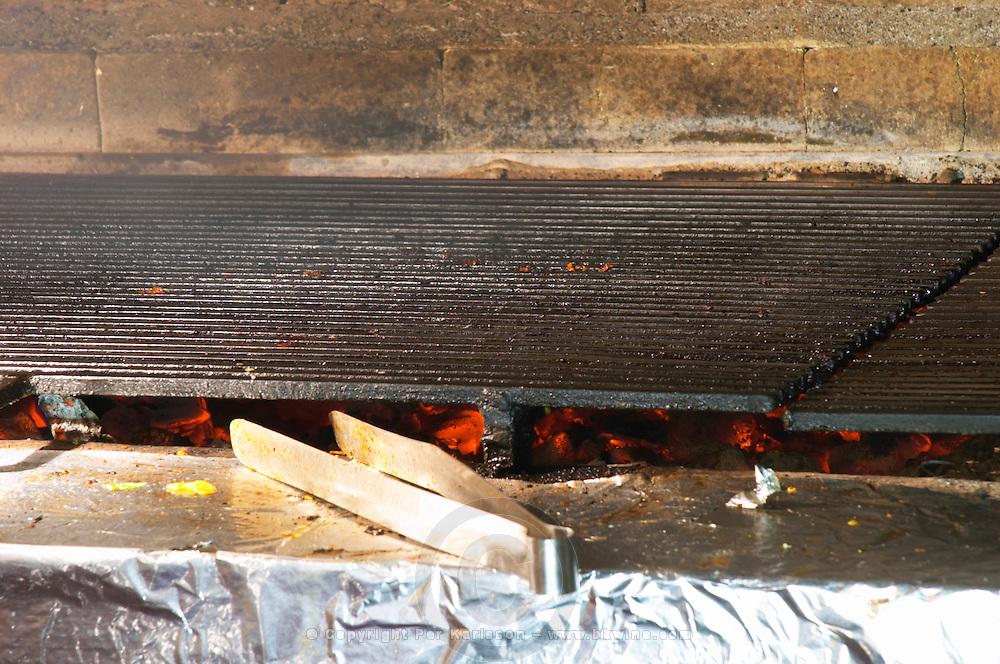 The winery restaurant: the char coal grill in black cast iron with a tool. Hercegovina Produkt winery, Citluk, near Mostar. Federation Bosne i Hercegovine. Bosnia Herzegovina, Europe.