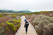 Young boy walking on boardwalk, Elfin Forest, Baywood Park, San Luis Obispos County, California, USA (MR)