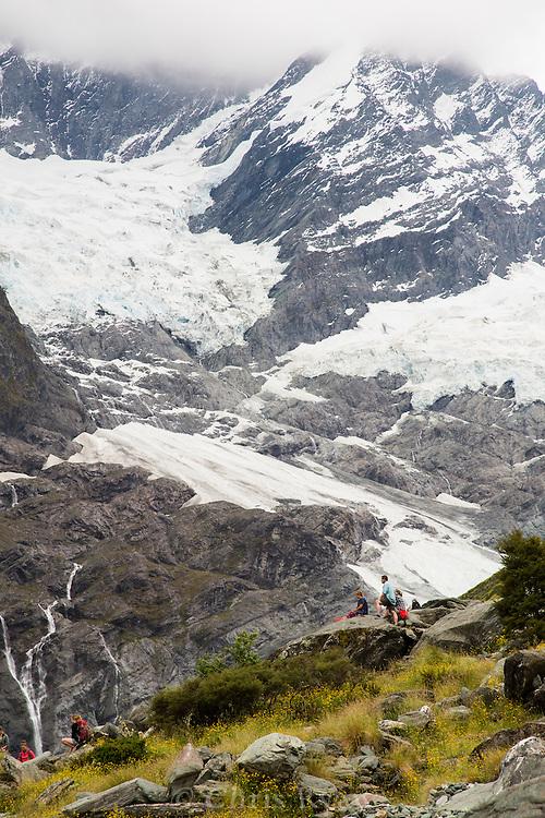 Hikers gazing at Rob Roy Glacier, Mt. Aspiring National Park, South Island, New Zealand