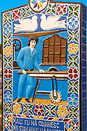 Tombstone of a timber mill worker,  The  Merry Cemetery ( Cimitirul Vesel ),  Săpânţa, Maramares, Northern Transylvania, Romania.  The naive folk art style of the tombstones created by woodcarver  Stan Ioan Pătraş (1909 - 1977) who created in his lifetime over 700 colourfully painted wooden tombstones with small relief portrait carvings of the deceased or with scenes depicting them at work or play or surprisingly showing the violent accident that killed them. Each tombstone has an inscription about the person, sometimes a light hearted  limerick in Romanian. .<br /> <br /> Visit our ROMANIA HISTORIC PLACXES PHOTO COLLECTIONS for more photos to download or buy as wall art prints https://funkystock.photoshelter.com/gallery-collection/Pictures-Images-of-Romania-Photos-of-Romanian-Historic-Landmark-Sites/C00001TITiQwAdS8