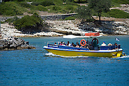 An small excursion boat full of tourists returning from Anti Paxos to Gaios harbour on the island of Paxos, The Ionian Islands, The Greek Islands, Greece, Europe