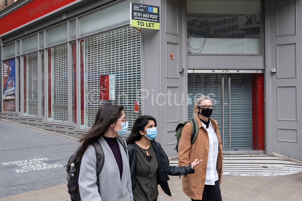 As numbers of Covid-19 cases in Birmingham have dramatically risen in the past weeks, increased lockdown measures are in place for Birmingham and other areas of the West Midlands, people wearing face masks pass closed down shops in the city centre on 7th October 2020 in Birmingham, United Kingdom. With financial difficulties for many businesses, and the country in recession, the downturn in the economy has left forced many shops to close down, leaving high streets in the UK struggling.